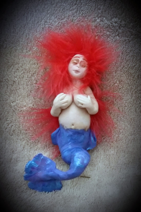 Little blue tailed mermaid with red hair made out of clay by Tina Parsons