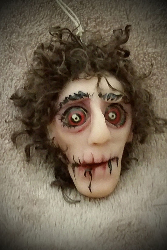Scary clay formed head with red eyes and brown hair by Tina Parsons